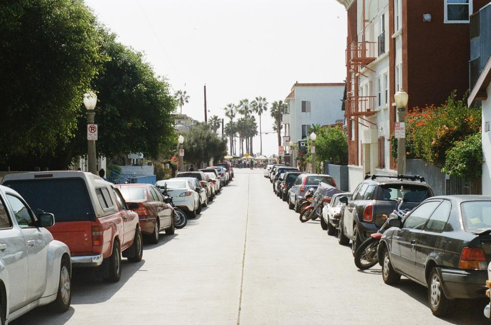 street, parking, cars, trucks, motorcycle, houses, apartments, buildings, palm trees, sunshine