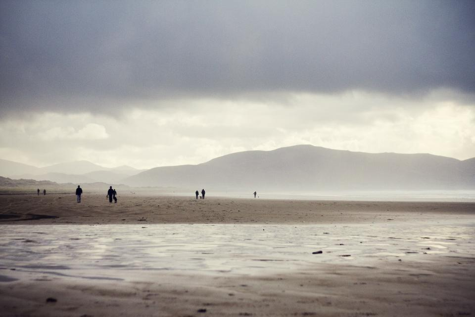 grey sky clouds mountains hills beach sand water people water