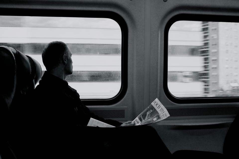 train, railway, transportation, travel, trip, black and white, people, man, sad, reading, newspaper
