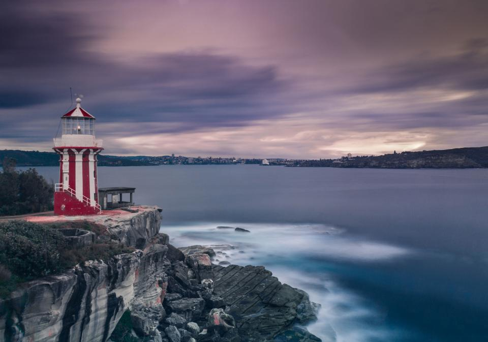 sea ocean water waves nature rocks cliff hill landscape clouds sky lighthouse building
