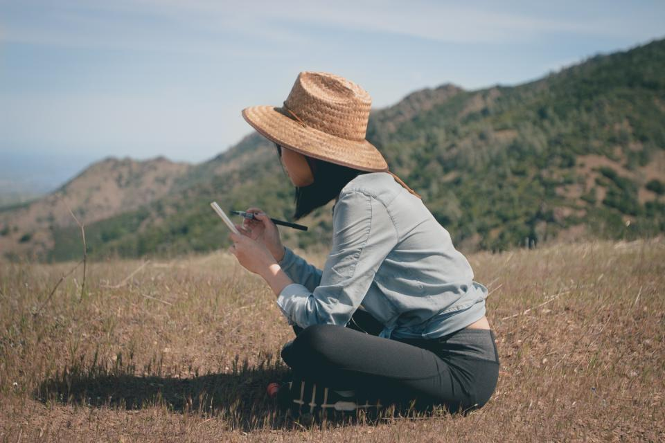 girl woman writing notepad thinking creative grass field nature outdoors hat mountains summer student