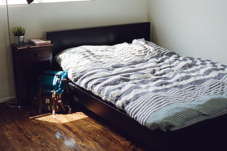 bedroom bed sheets covers night table nightstand hardwood bag knapsack backpack book sleep