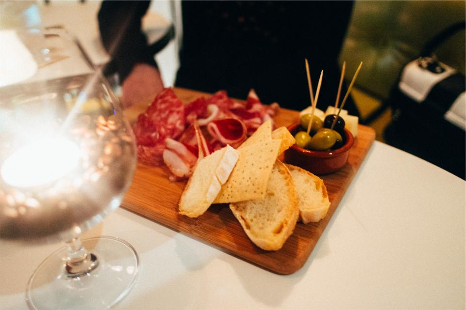 food appetizers cutting board bread cheese olives toothpicks cured meat cold cuts wine glass eating
