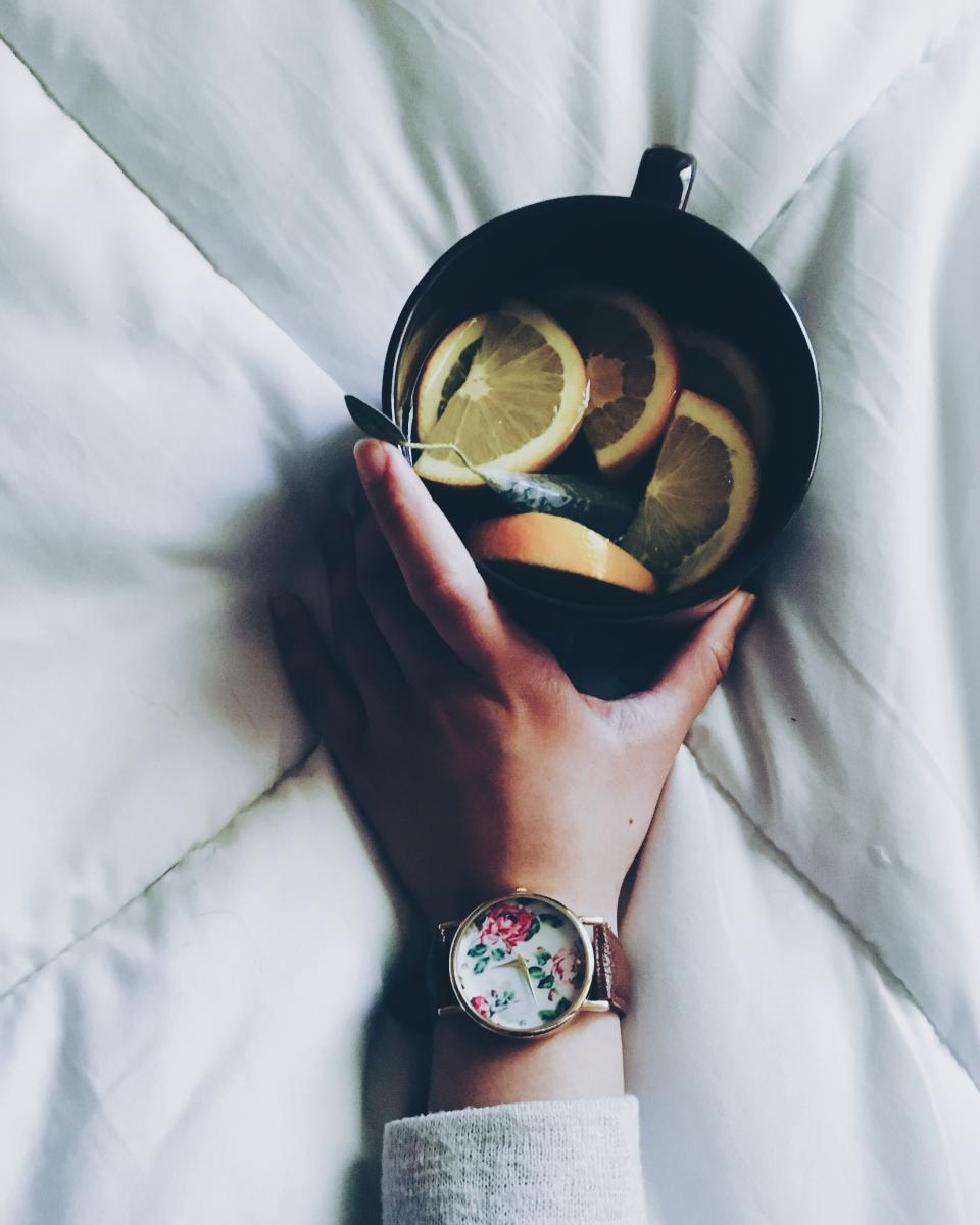 hand black cup mug lemon fruit drink tea white bed sheet relax