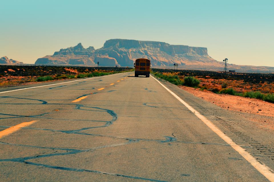 school bus road pavement desert sand plants rural mountains cliffs sunshine hot