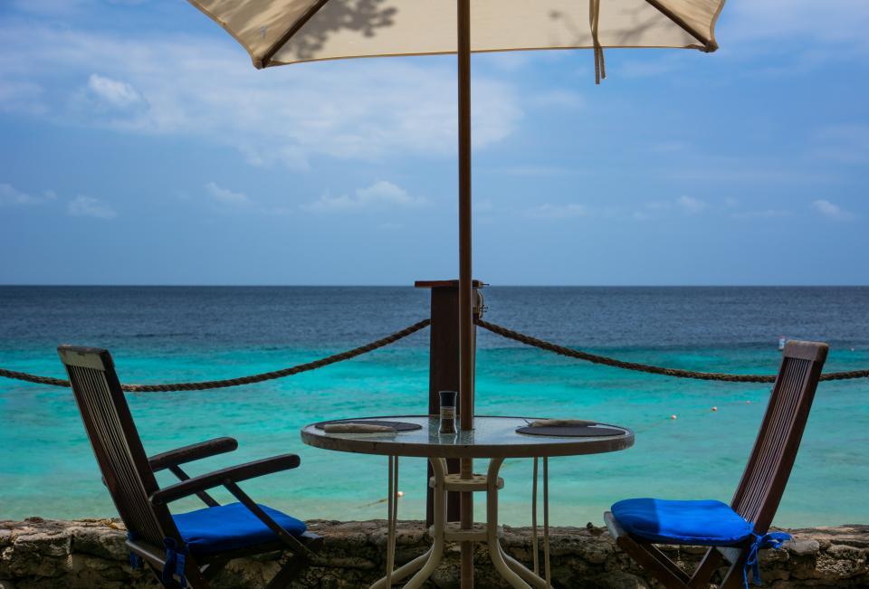 patio chairs table umbrella beach sand ocean sea tropical sky paradise