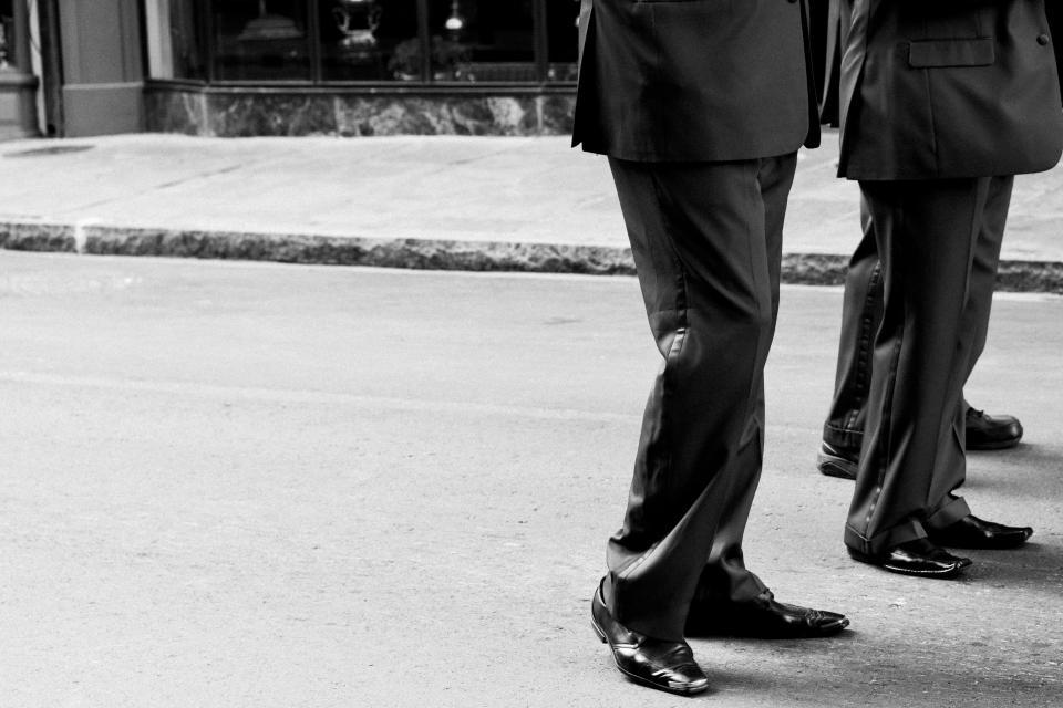 men suites pants dress shoes street sidewalk pavement black and white