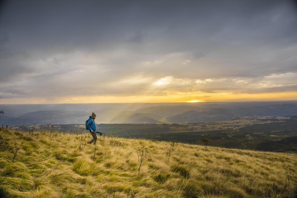 guy, man, hiking, trekking, grass, fields, mountains, landscape, adventure, outdoors, nature, sky, clouds, cloudy, storm, sun rays, sunbeams, walking, fitness