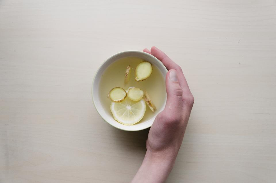 tea lemon ginger drink hot hand beverage cup bowl wood table