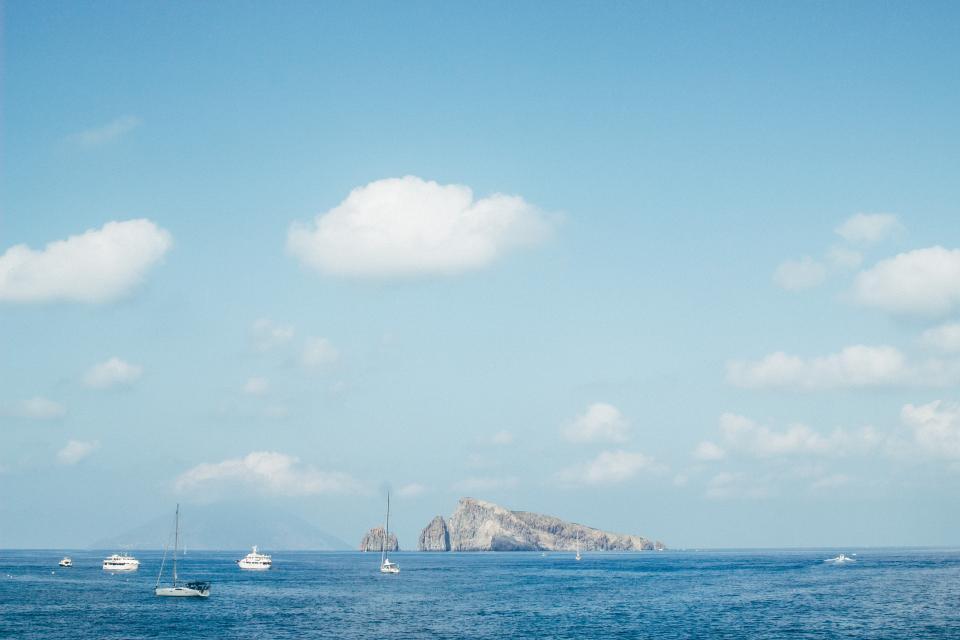 sea, ocean, water, wave, nature, boat, ship, sailing, transportation, travel, fishing, horizon, island, blue, sky, clouds