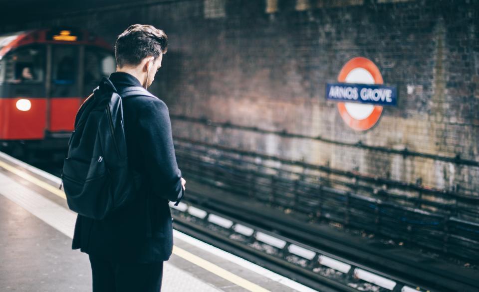 people man train station travel alone adventure earphones music sound black back pack rail subway