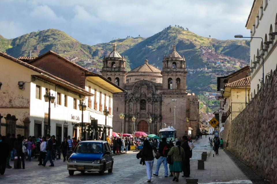 Cusco Peru streets people pedestrians sidewalk cobblestone buildings architecture city town mountains hills