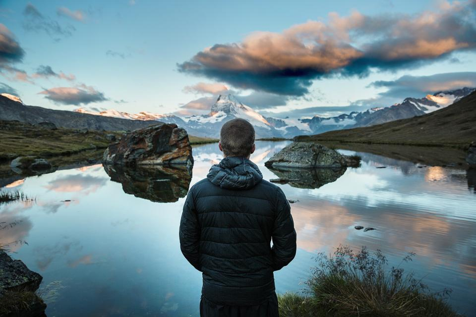 guy man people landscape mountains nature river water reflection sky clouds hills valleys jacket coat adventure outdoors
