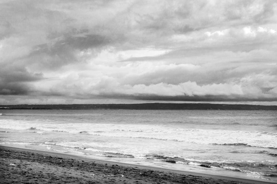 black white grey sky clouds water beach waves sand water sea ocean