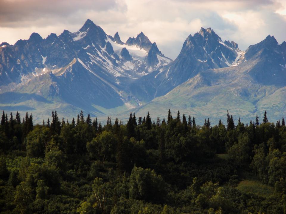 alaska landscape mountains peaks valleys cliffs snow trees woods forest nature sky clouds