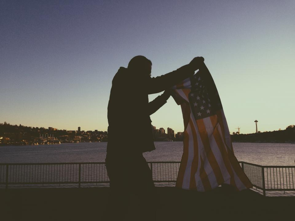flag, american, usa, united states, man, guy, sunset, dusk, water, railing, buildings, skyline