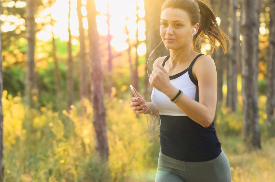 人々の女性運動フィットネスジョギング実行イヤホン音楽サウンド携帯電話のiPodの服朝の太陽日当たりの良い森