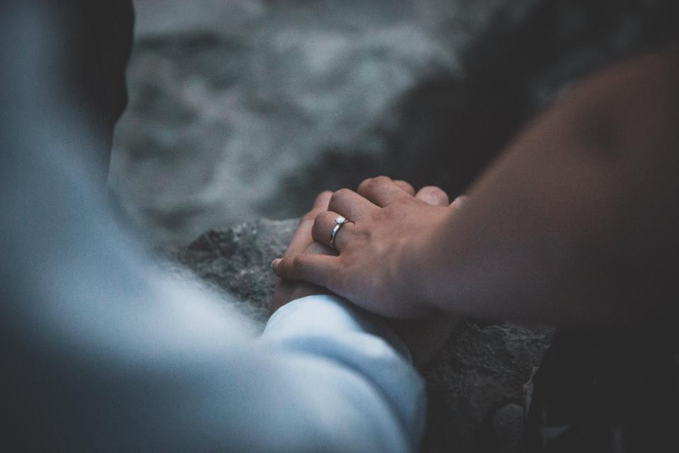 people man woman couple ring engagement blur holding hands
