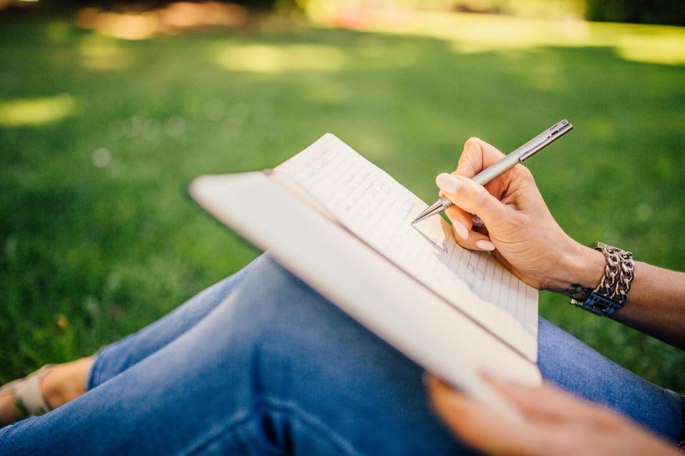 writing writer notes pen notebook book girl woman people hands grass outdoors