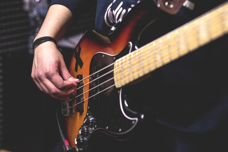 crafts hobby music instrument guitar strum play guy man people hands fingers still bokeh
