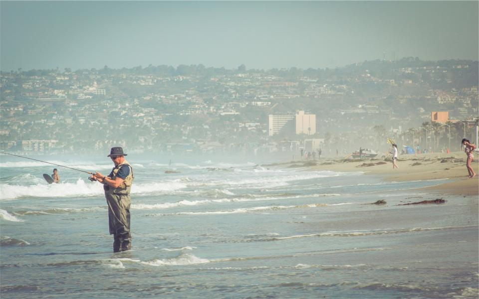 man, fishing, fisherman, hat, beach, sand, water, waves, shore, people, sunshine, summer, kid, boy, houses, hills