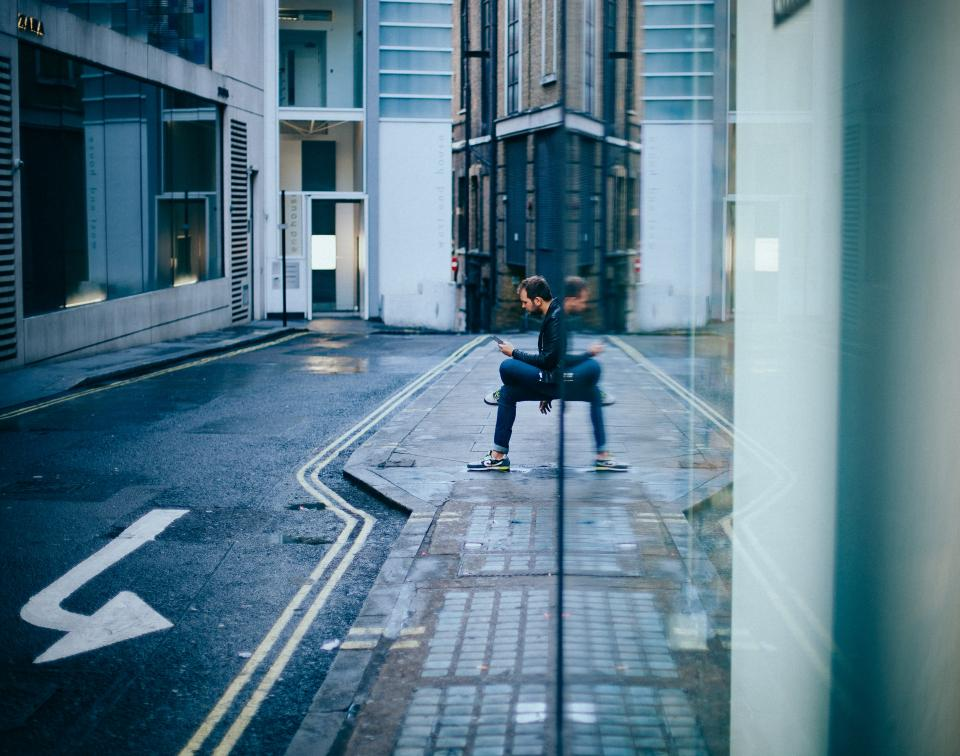 building, architecture, road, street, sidewalk, people, guy, man, sitting, waiting, texting, wall, reflection