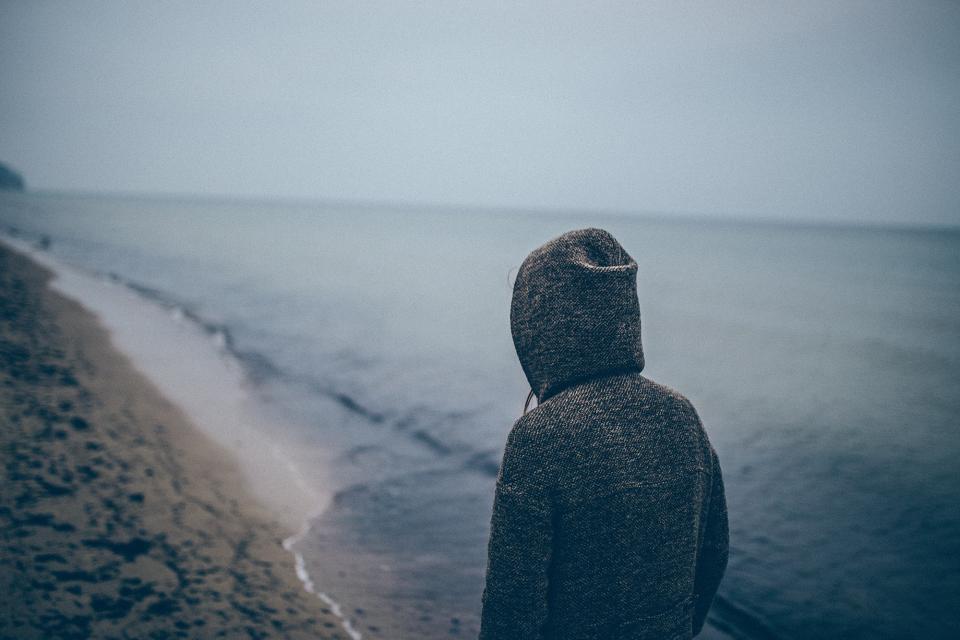 dark grey sky water beach sand shore hoodie boy guy man sweater sea ocean