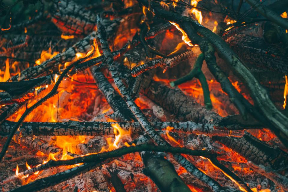 still camp fire flames hot burning wood charred ashes light shadows