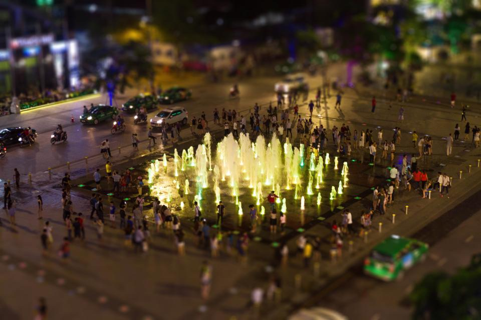 fountain park water lights blur car vehicle city people crowd men women city urban