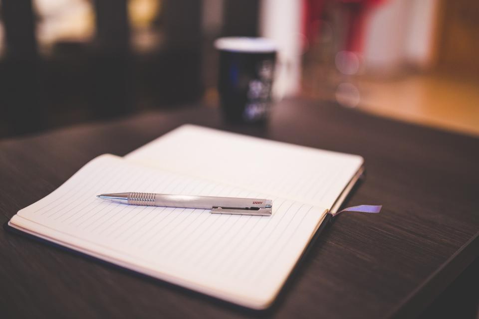 pen notebook paper write work desk mug bokeh