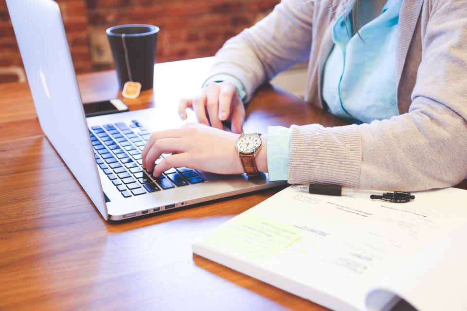 business working office desk laptop macbook computer technology typing paper tea cup mug startup