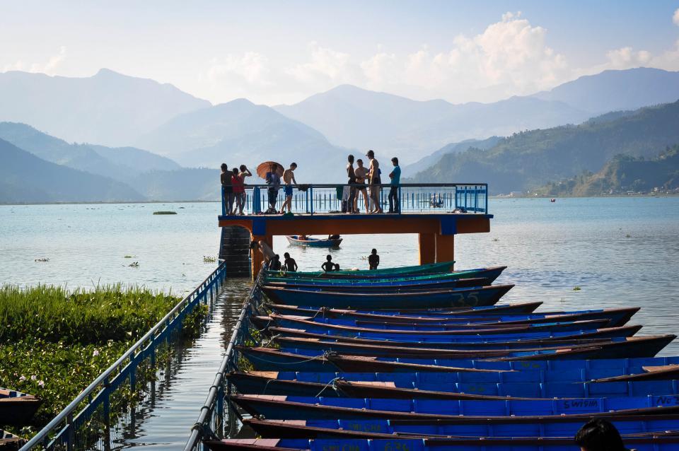 boats docks pier water swimming people kids lake water mountains hills Fewa Lake Pokhara Nepal