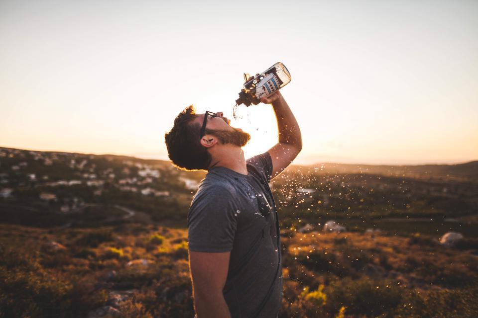 guy man drinking water water bottle thirsty beard glasses people sunshine sunset tshirt outdoors hiking