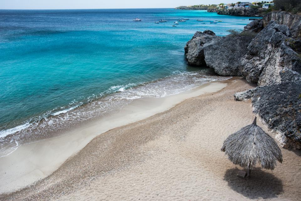 beach sand water ocean sea tropical caribbean paradise coast rocks umbrella boats