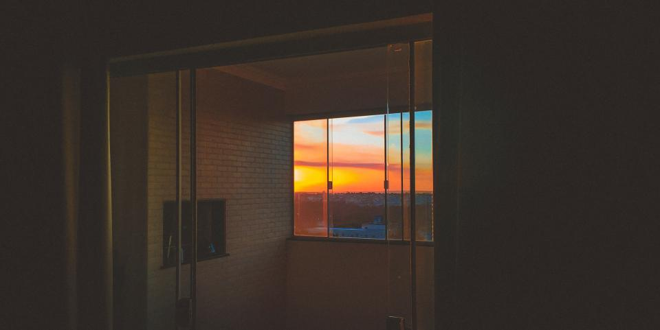 bricks wall glass window sunset sky clouds panes house room view buildings