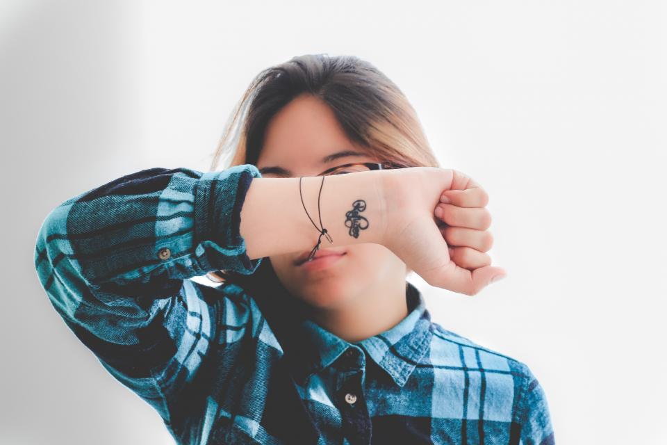 人々の女性の入れ墨の手フランネルの眼鏡の手青いチェッカー