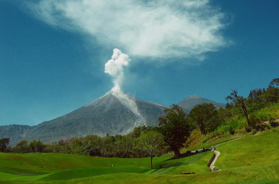 voclano, smoke, ash, mountain, golf course, fairway, green, hole, pin, trees, grass, outdoors, sky, blue