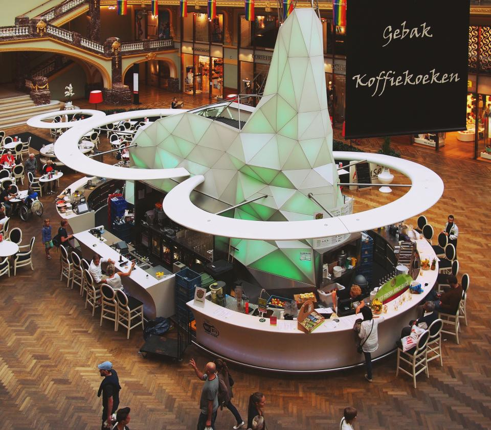 shopping mall stores restaurant tables chairs bar people walking architecture