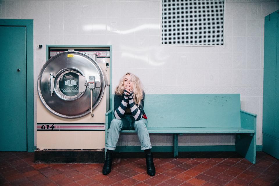 people woman sit laundry machine shop denim blue alone blonde fashion