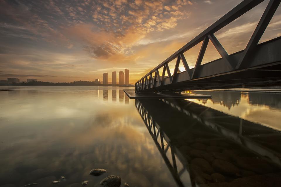 nature landscape water steel bridge water rocks reflection city urban skyline sky clouds horizon