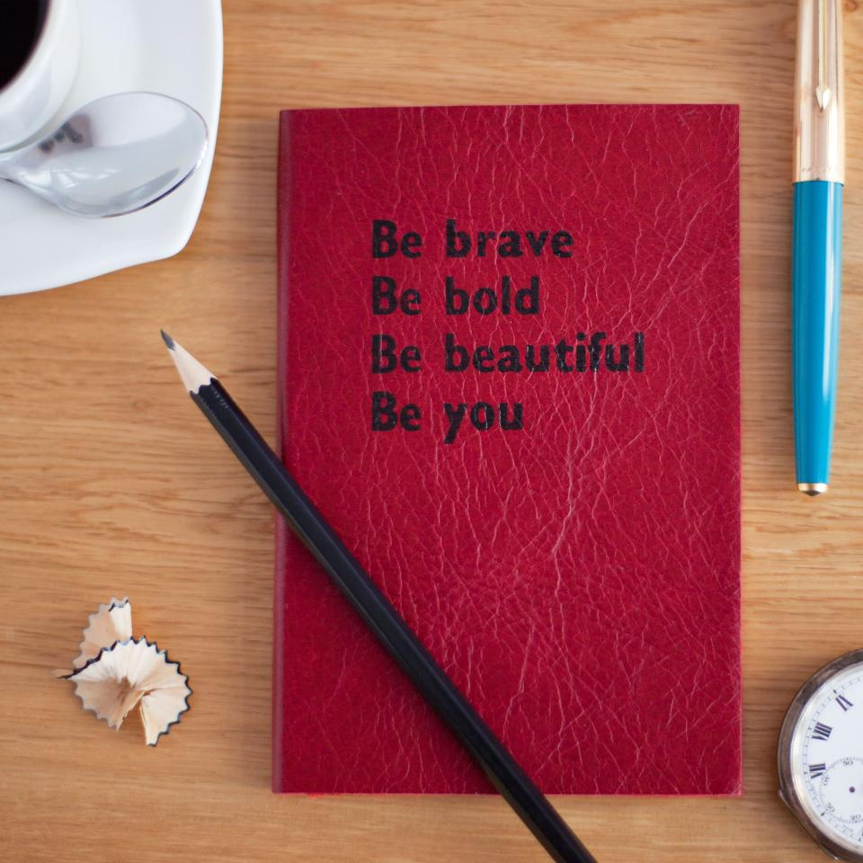 still items things book notebook journal excerpt quote saying be bold be brave be beautiful be you pencil shavings retractable office work wood table clock cup saucer teaspoon coffe bokeh