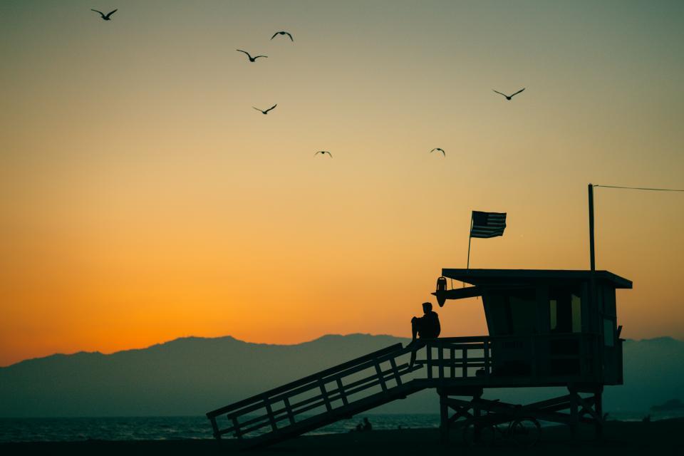 birds, flying, animal, sky, sunset, sunrise, mountain, hut, cottage, sea, ocean, water, beach, coast, shore, flag, usa, bike, bicycle, people, man, lifeguard, coastguard, silhouette