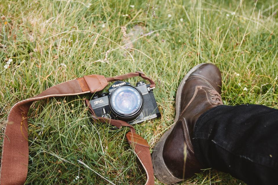 camera accessory canon photography green grass outdoor travel shoe footwear jeans