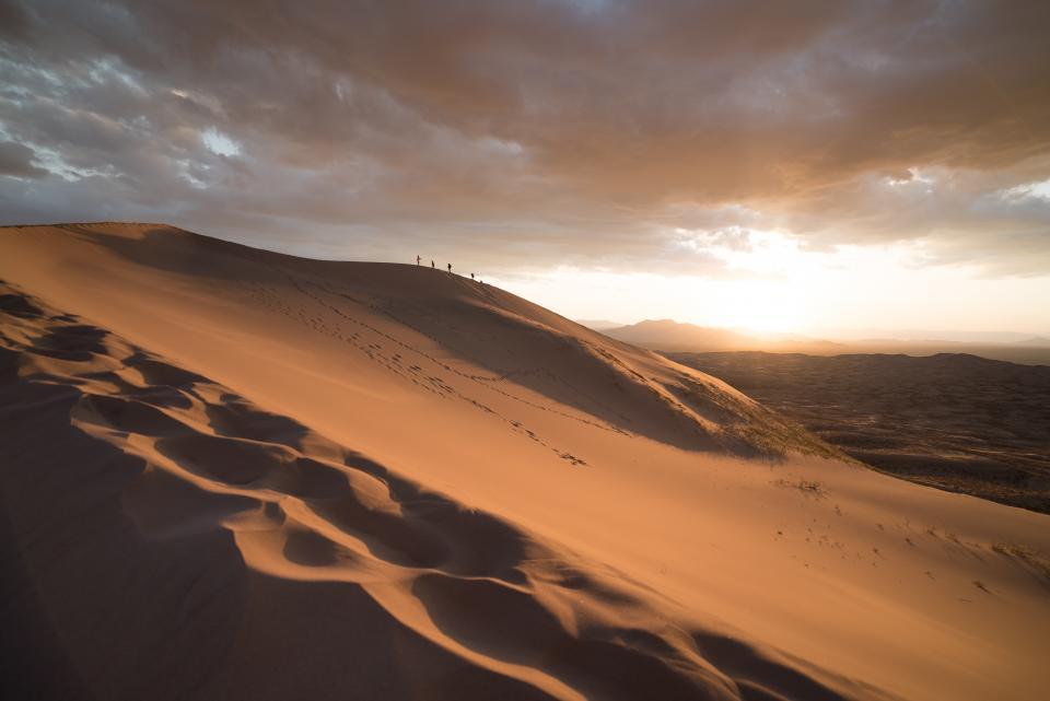 desert sand dunes outdoors landscape hills mountains nature sunset sky clouds