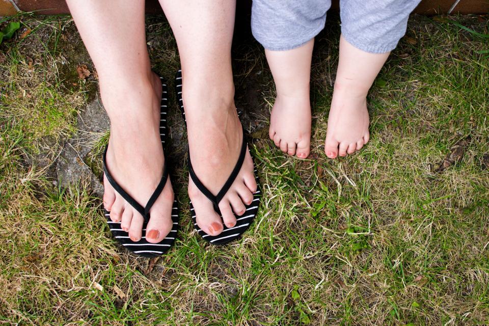 緑の草の足の母の赤ちゃんの足