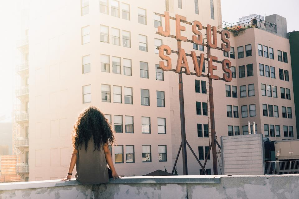 urban, city, buildings, sun, sunlight, people, girl, lady, woman, curly, hair, sitting, jesus