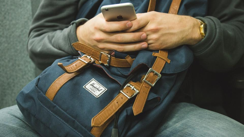iphone texting mobile smartphone cell phone technology hands backpack knapsack people student