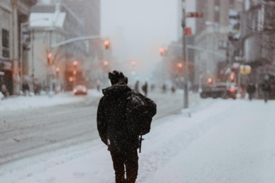 city urban road snow winter cold weather people man walking alone travel traffic light