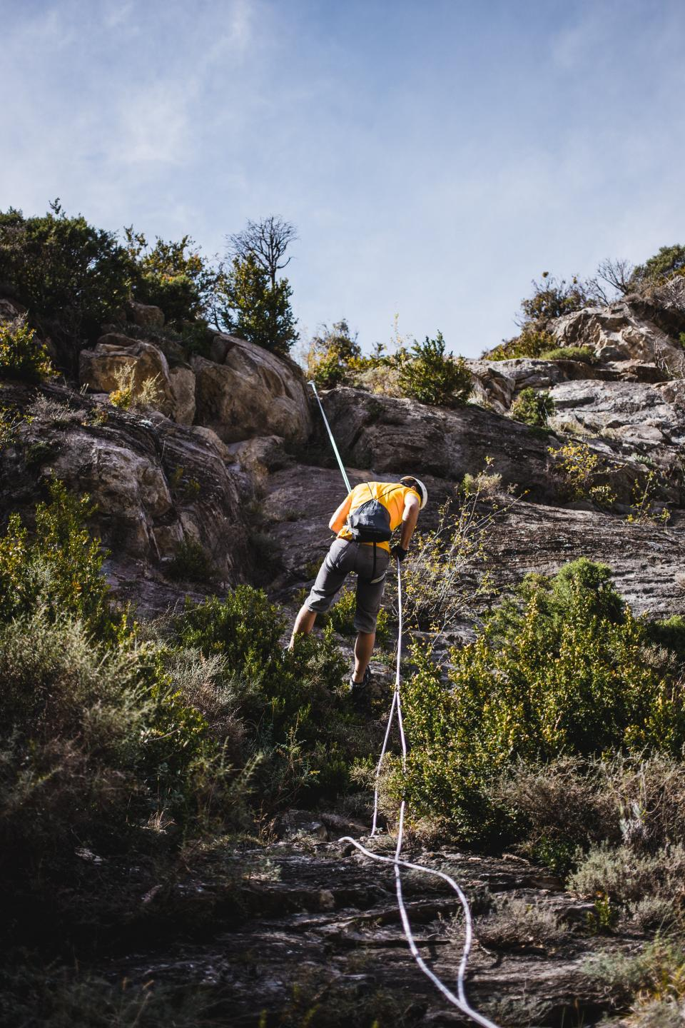 people man guy adventure cliff rocks hill mountain landscape rappelling rope fitness health outdoor travel sky green grass trees plants