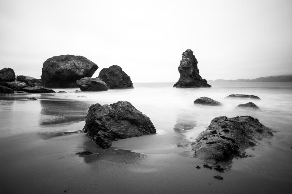 sea ocean water waves nature sand beach coast shore rocks cliff sky horizon black and white